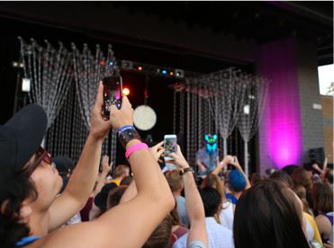 People taking pictures at a concert with phones