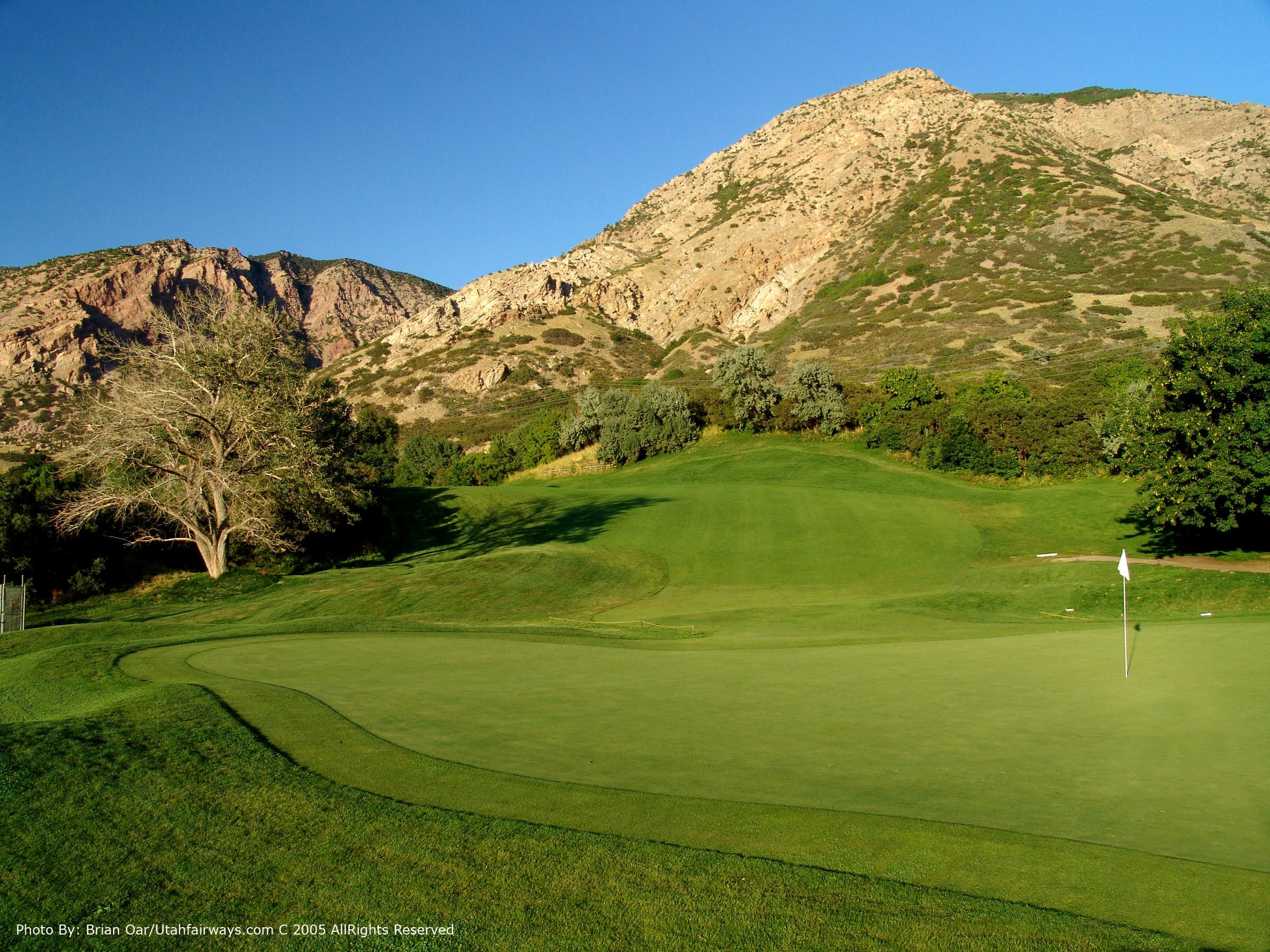 One of the greens at Mount Ogden Golf Course with a mountain in the background.