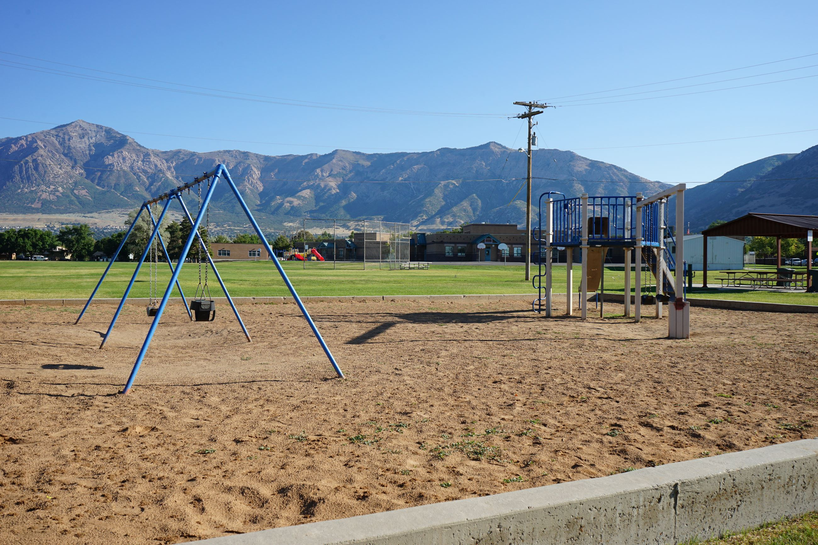 A playground with a swing set and slides with mountains in the background